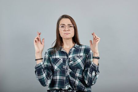 Young brunette girl blue green in checkered shirt on grey background woman crossing her fingers and wishing for good luck Фото со стока