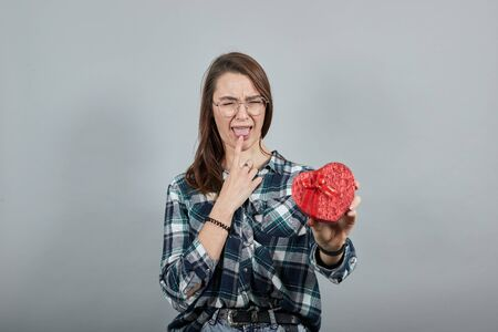 Young brunette girl blue green in checked shirt on grey background upset woman in glasses holds gift red box in the shape of heart, touches her index finger to tongue Фото со стока