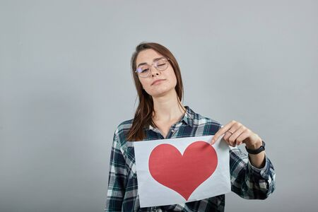 Young brunette girl blue green in checked shirt on grey background an offended woman holds piece of paper with a red heart, a negative attitude in her hand