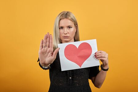 Young blonde girl in black dress on yellow background confident woman holding piece of paper with red heart hand shows stop