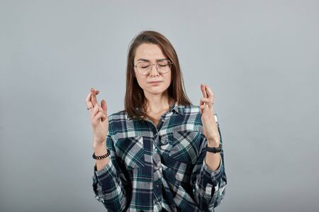 Young brunette girl blue green in checked shirt on grey background woman in glasses hopes for luck crossed her fingers