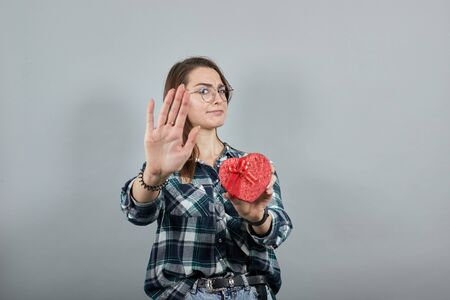 Young brunette girl blue green in checked shirt on grey background insulted woman holds gift red box in the form of heart, stops with palm of her hand as stop sign