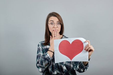 Young brunette girl blue green in checked shirt on grey background a shocked woman with glasses holds piece of paper with red heart in her hand, covering mouth with hand Фото со стока