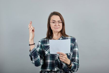 Young brunette girl blue green in checked shirt on grey background excited woman in glasses holds a white sheet of paper in her hand, crosses fingers Фото со стока