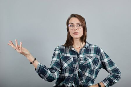 Young brunette girl blue green in checked shirt on grey background a happy woman listens to music on headphones, gestures with hand in displeasure