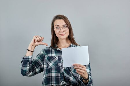 Young brunette girl blue green in checked shirt on grey background happy woman with glasses holds a white sheet of paper in her hand, shows herself