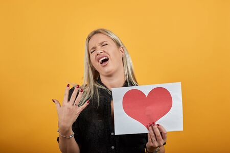 Young blonde girl in black dress on yellow background, an angry woman holds piece of paper with red heart in her hand and demonstrates emotions Фото со стока