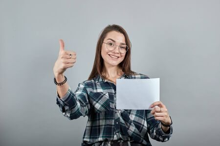 Young brunette girl blue green in checked shirt on grey background happy woman with glasses holds a white sheet of paper in hand, shows her thumb Фото со стока