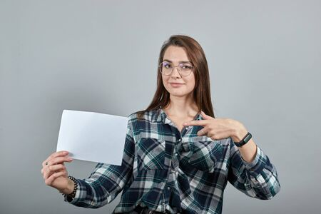 Young brunette girl blue green in checked shirt on grey background, happy woman holds a white piece of paper in hand and shows it with index finger Фото со стока
