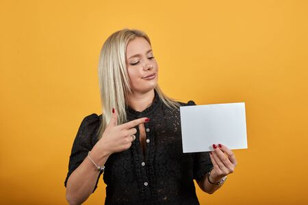 Young blonde girl in black dress on yellow background stylish woman holds an empty sheet of blank paper in hand points with index finger