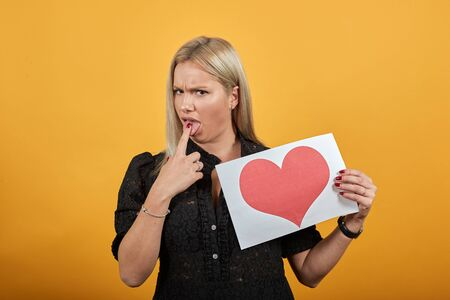 Young blonde girl in black dress on yellow background angry woman holds piece of paper with red heart in hand shoves finger in mouth Фото со стока