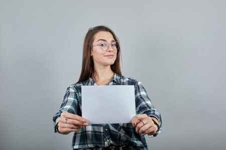 Young brunette girl blue green in checked shirt on grey background happy woman with glasses holding a white sheet of paper, smiling