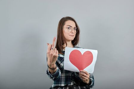 Young brunette girl blue green in checked shirt on grey background angry woman holds piece of paper with red heart, shows the middle finger