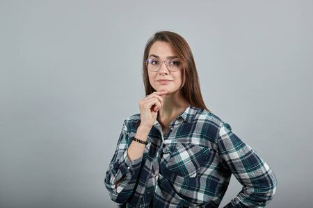 Young brunette girl blue green in checked shirt on grey background smart woman with glasses thinks, holds her chin with hand