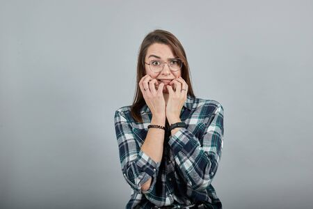 Young brunette girl blue green in checked shirt on grey background frightened woman with glasses is afraid, holds hands near mouth Фото со стока