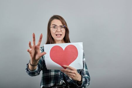 Young brunette girl blue green in checked shirt on grey background a terrified woman holds piece of paper with red heart and reacts