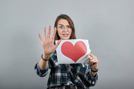 Young brunette girl blue green in checked shirt on grey background a dissenting woman in glasses holds piece of paper with a red heart in her hand, stops with hand