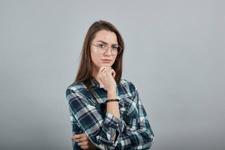 Young brunette girl blue green in checked shirt on grey background smart woman with glasses thinks, makes decisions stole her head on hand Фото со стока
