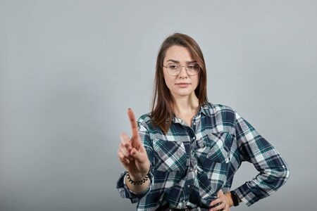 Young brunette girl blue green in checked shirt on grey background woman in glasses counteracts by shaking her index finger, a sign of disagreement