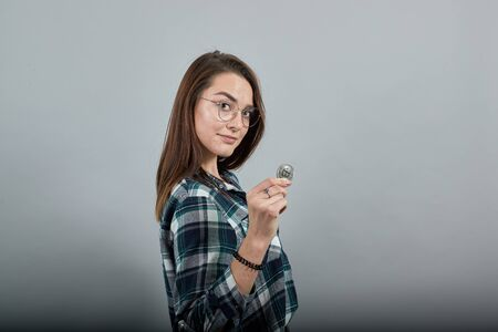 Young brunette girl blue green in checked shirt on grey background stylish woman in glasses shows off bitcoin coin