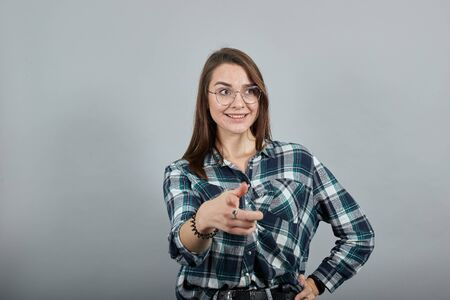 Young brunette girl blue green in checked shirt on grey background happy woman with glasses shows her index finger