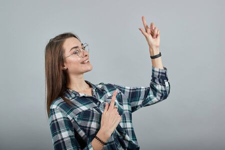 Young brunette girl blue green in checked shirt on grey background happy woman with glasses smiles, gestures with her hands