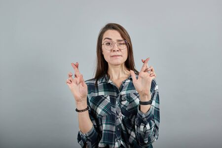 Young brunette girl blue green in checked shirt on grey background a woman with hope in glasses crossed her fingers for luck