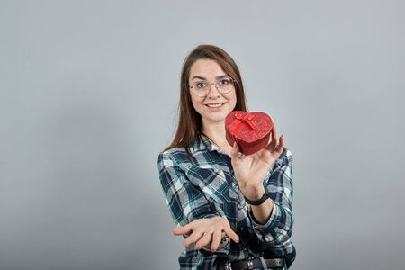 Young brunette girl blue green in checked shirt on grey background, happy woman with glasses holds gift box in form of a red heart in her hand