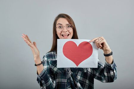 Young brunette girl blue green in checked shirt on grey background happy woman with glasses holding a piece of paper with red heart, hand gestures Фото со стока