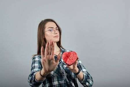 Young brunette girl blue green in checked shirt on grey background dissatisfied woman in glasses shows gift in form of red heart, gesture stop with the palm of her hand. Фото со стока