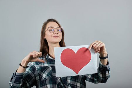 Young brunette girl blue green in checked shirt on grey background happy woman with glasses holding a piece of paper with red heart, pointing with her finger