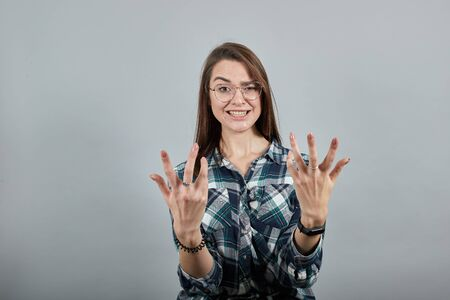 Young brunette girl blue green in checked shirt on grey background irritated woman with glasses shakes her hands