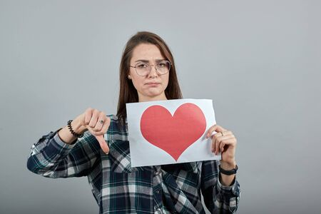 Young brunette girl blue green in checked shirt on grey background disappointed woman in glasses holds piece of paper with red heart, turned her thumb down Фото со стока