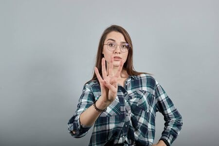 Young brunette girl blue green in checked shirt on grey background confident woman in glasses shows four fingers