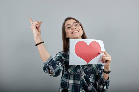 Young brunette girl blue green in checked shirt on grey background a happy woman in glasses holds a piece of paper with red heart, shows her index finger