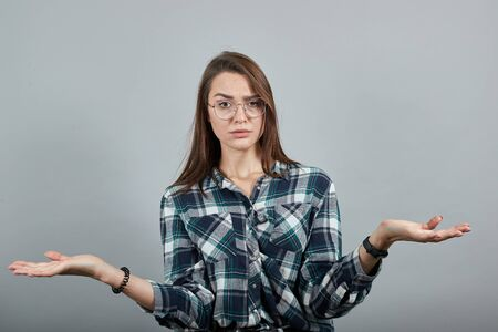 Young brunette girl blue green in checked shirt on grey background shocked woman spreads her hands