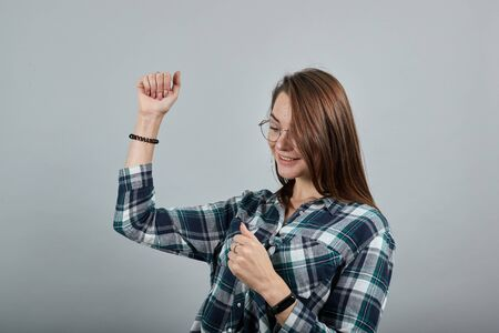 Young brunette girl blue green in checked shirt on grey background happy woman with glasses dancing Фото со стока