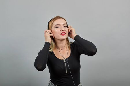 Young blonde girl in black jacket on grey background happy woman listening to music with headphones and smiling