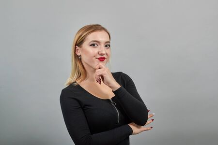 Young blonde girl in black jacket on grey background conceived by a woman holding her hand to chin Фото со стока