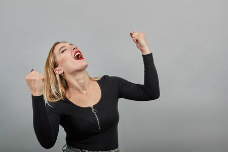 Young blonde girl in black jacket on grey background happy woman reacts with a smile raises her hands up