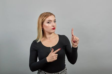 Young blonde girl in black jacket on grey background smart woman thinks, moves her index fingers
