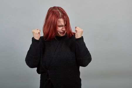 Young redhead fat lady in black sweater on grey background upset woman put her hands in fists and raised them