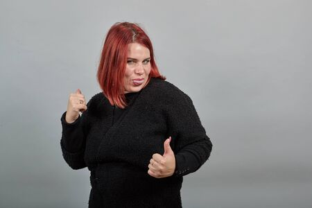 Young redhead fat lady in black sweater on grey background funny woman shows tongue and holds thumbs up