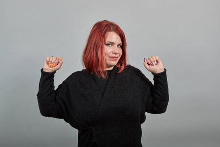 Young redhead fat lady in black sweater on grey background happy woman raises her hands in delight and smiles Banco de Imagens