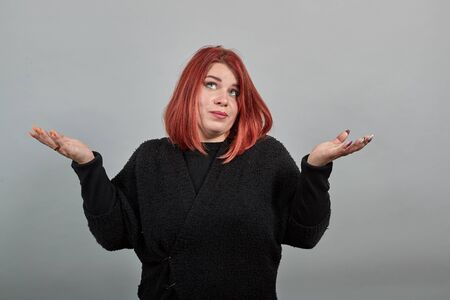 Young redhead fat lady in black sweater on grey background a woman looks up mountain and shikoro spreads hands, gesturing with them