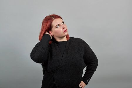 Young redhead fat lady in black sweater on grey background smart woman thinks, holds her hand over head