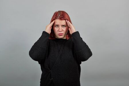 Young fat redhead lady in black sweater on grey background a poor woman suffering from a headache, head hurts