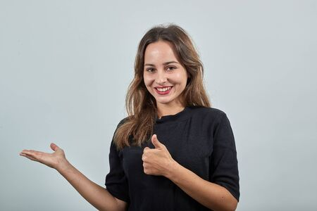 Cute young brunette woman in black t-shirt, blue jeans with belt on gray background, happy smiling girl gives a thumbs up and points the direction with hand