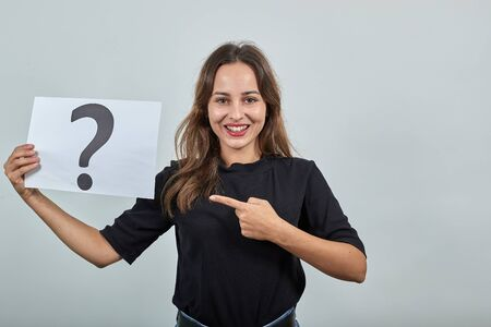 Cute Young Brunette Woman In Black T-Shirt, Blue Jeans With Belt On Gray Background, Happy Girl Smiling Holding Piece Of Paper With Question Mark In Hand And Pointing Index Finger In The Direction