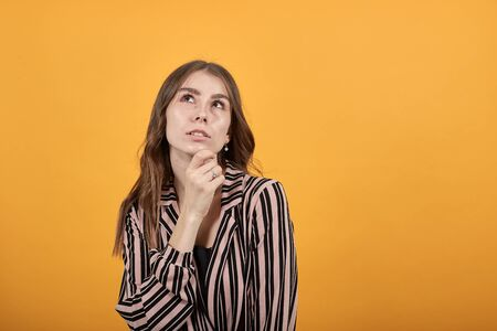 Cute Young Woman Light Brown In Striped Pink, Black Shirt On A Yellow Background, Conceived Girl Touches Her Chin And Looks Up. Concept Of The Smart People